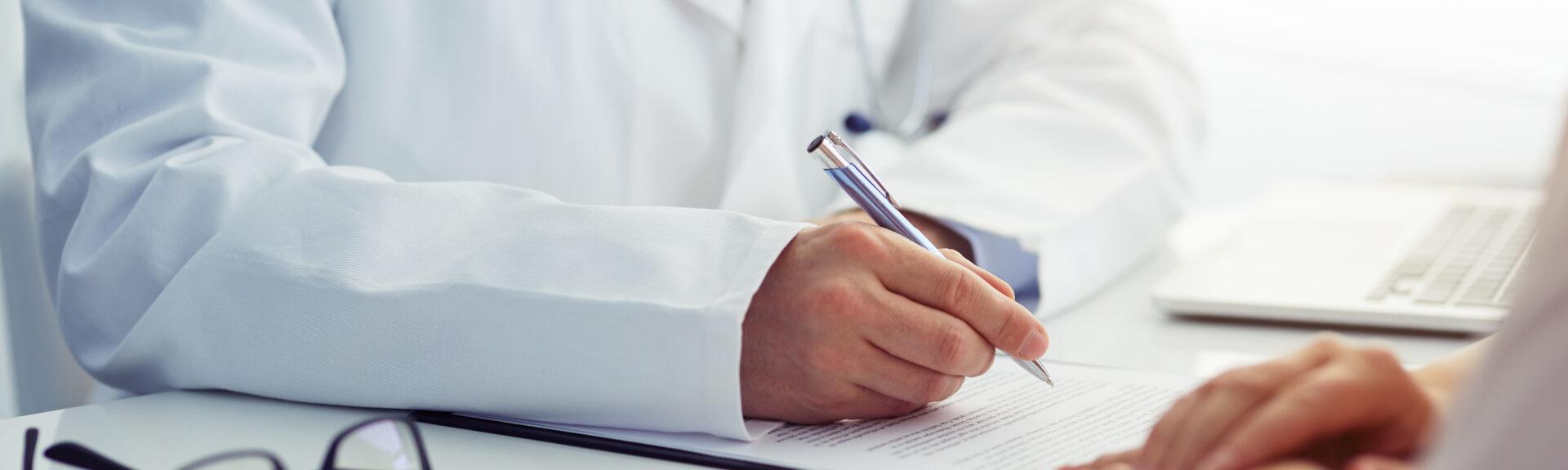 Arzt schreibend am Arbeitstisch
