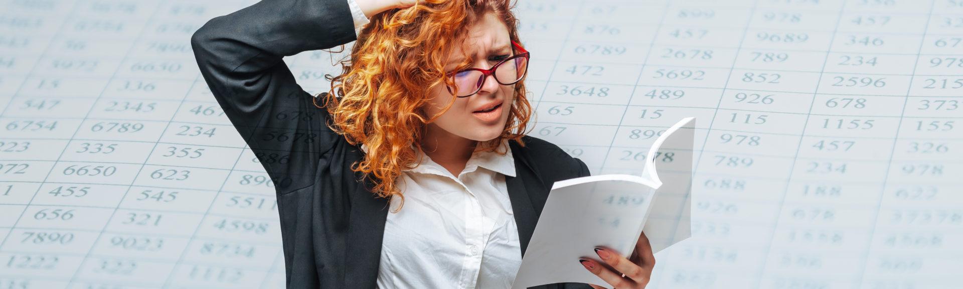 Eine Dame mit Brille hält ein Buch oder Skript und liest vertieft