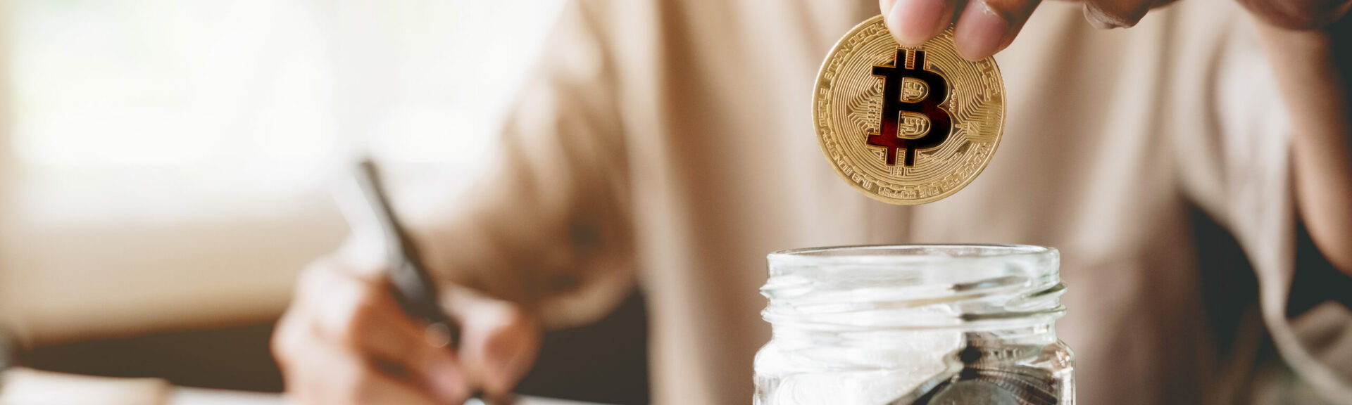 A person sitting at her desk and holding a bitcoin