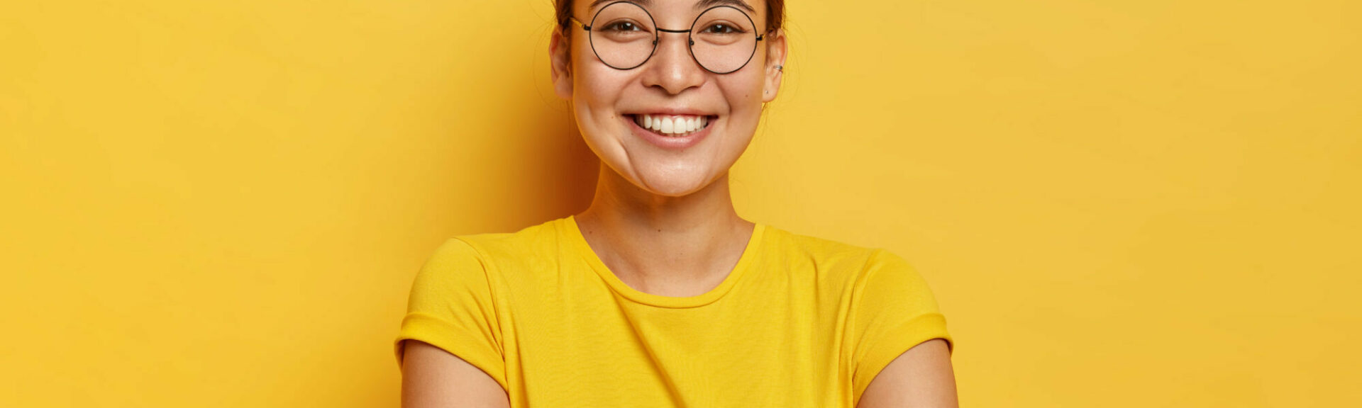Isolated shot of pleased cheerful woman with eastern appearance, smiles broadly, being in good mood, entertained by funny friends, dressed casually, wears big transparent glasses, isolated on yellow