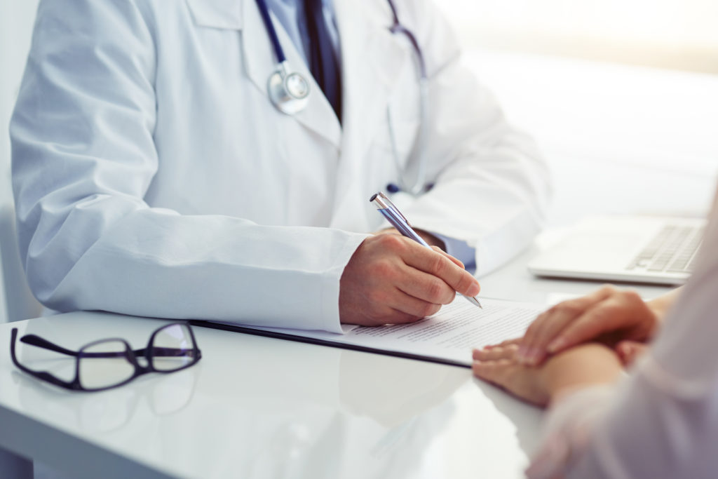 Doctor consults with his patient and writes notes on the clipboard